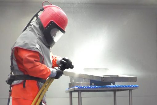 A worker uses an aqua blasting machine to finish 304 grade stainless steel for use in drum handling equipment.
