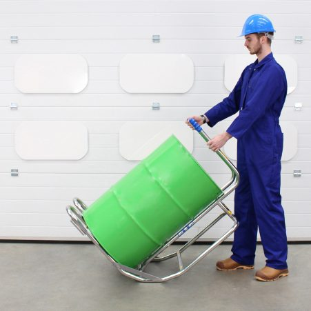 An operator handling a drum rollover cradle and drum