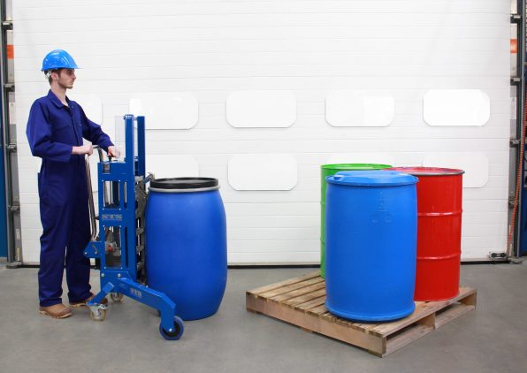 An operator using the STS Corner Drum Depalletiser to lift drums and barrels onto a pallet