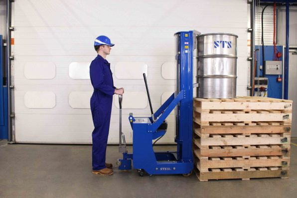 Operator lowers open top drum onto raised platform with the drum stacker.