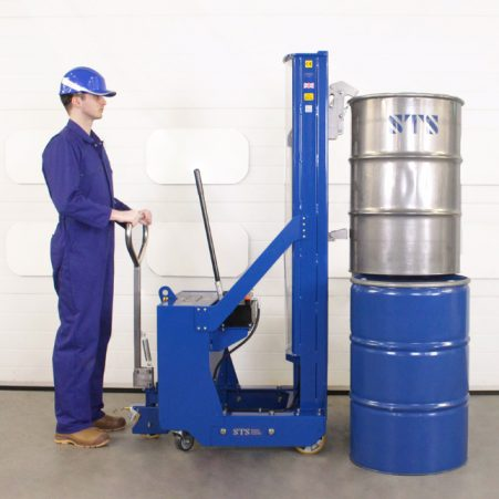 Operator uses the drum stacker to load a steel open-top drum vertically on top of another drum.
