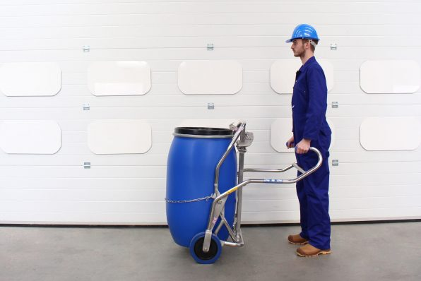 An operator moves a barrel using the plastic drum trolley.