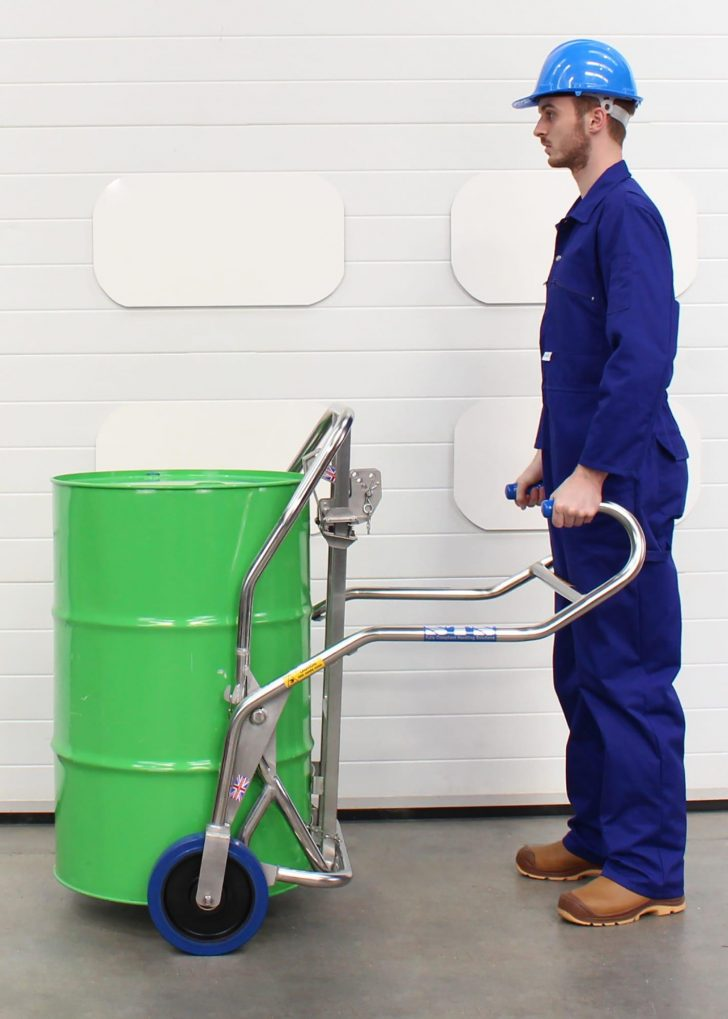 A man moves a steel drum with the drum trolley