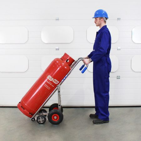 Operator using a cylinder trolley to move a propane bottle