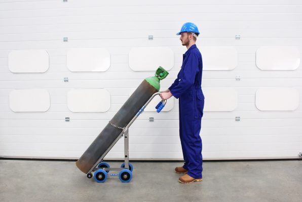 An operator using the STS Gas Cylinder Trolley to transport gas cylinders
