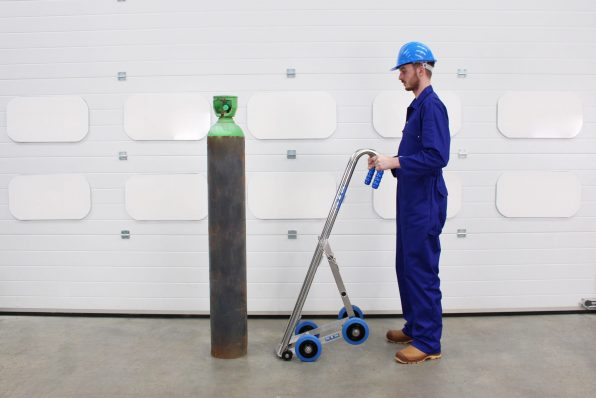 An operator preparing to load a gas cylinder onto the Gas Cylinder Trolley