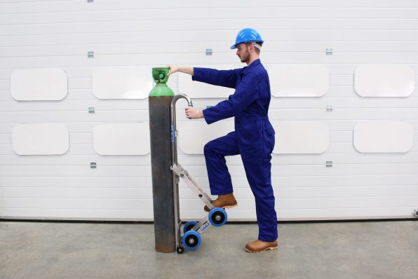 An engineer loading the gas cylinder onto the STS Gas Cylinder Trolley