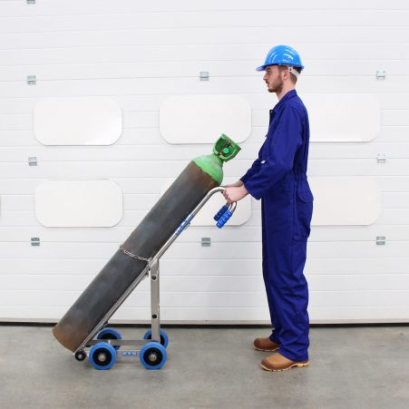 An operator using the STS Gas Cylinder Trolley for transporting gas cylinders