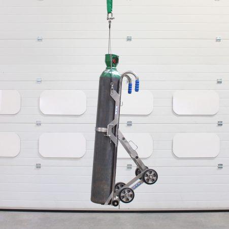 A gas bottle trolley lifted using a hoist on a crane