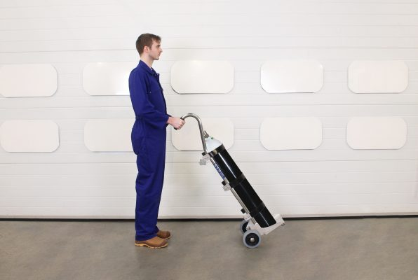 Porter moves gas cylinder using medical trolley.