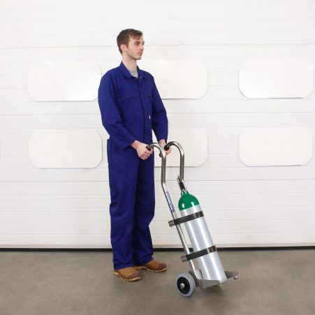 Operator uses medical gas cylinder trolley to manoeuvre a oxygen bottle