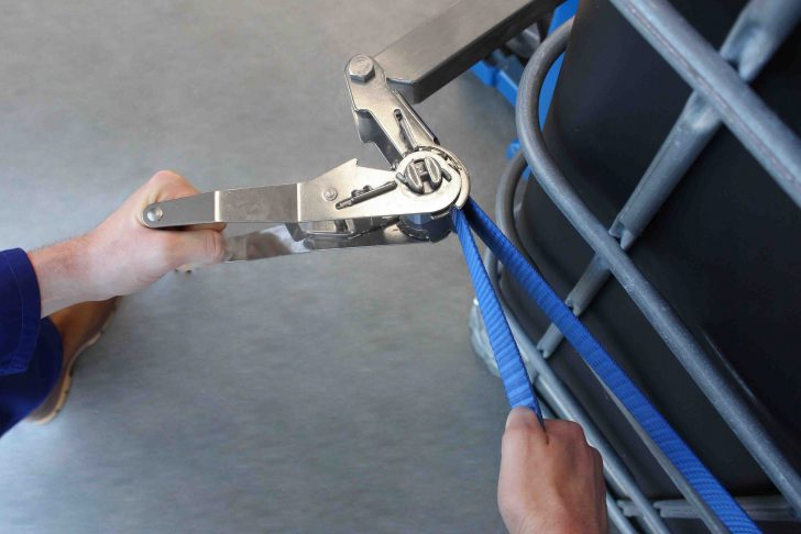 Operator uses stainless steel ratchet a strap to secure a IBC on the ITM01 IBC Tilter & Tipper