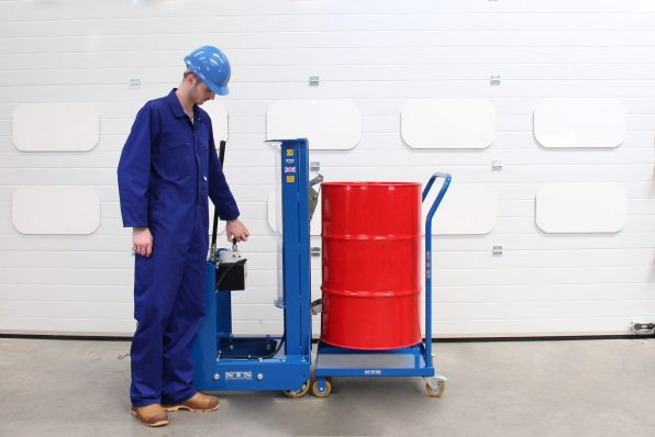 An operator lowers a drum onto the oil drum dolly using a drum-lifting unit.