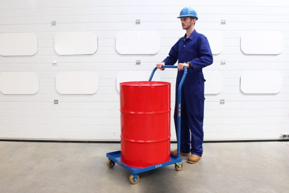 An operator uses the drum dolly with handle to move a red steel 205L drum.